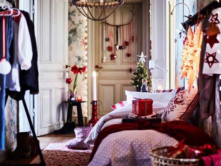 Udekorowana sypialnia z białą/czerwoną pościelą, dużą gwiazdą bożonarodzeniową, świecznikiem na podłodze i opakowanymi prezentami.