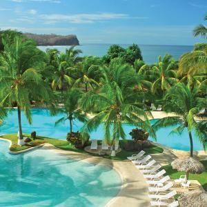 Las hotels en la playa con los árboles. Tiene mucho las sillas blancos.