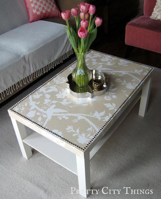 A 20 dollar IKEA plain white coffee table...pick your wallpaper print, spray adhesive to get it to stick...apply mod podge and spray shellac over the wallpaper as a protective coating...and lastly, add decorative nails as a border.