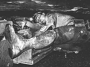 Miner working in a confined, cramped position inside a narrow coal seam on a…