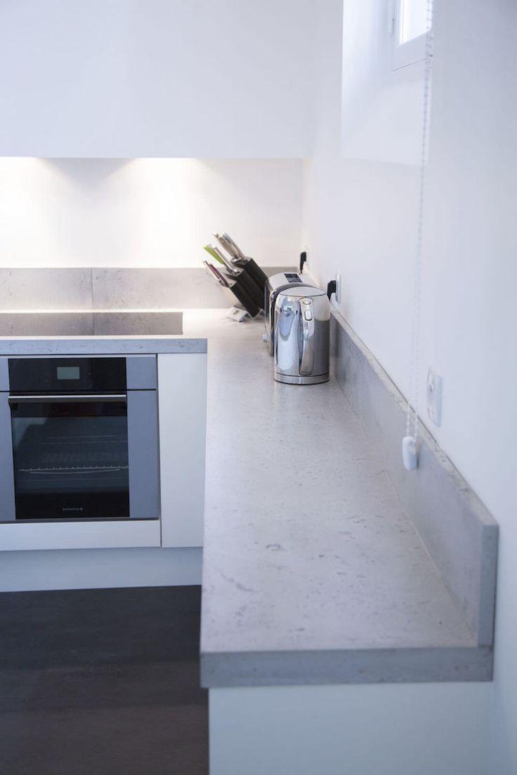 plan de travail en béton ciré, armoires de cuisine blanches et appareils inox