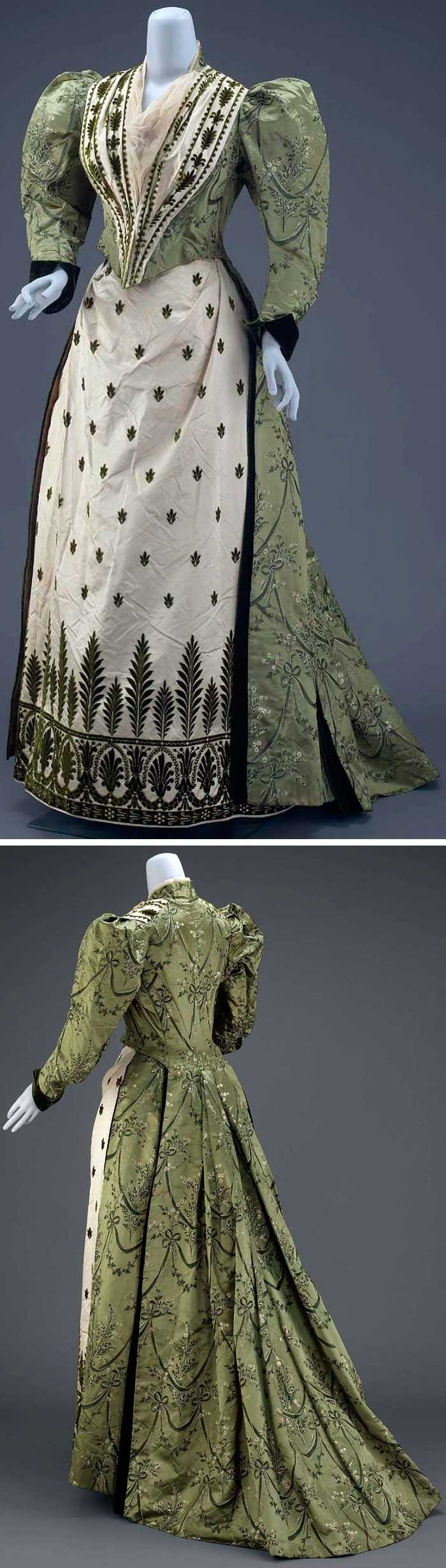 Circa 1888-1890 two-piece dress. Overdress: sage green compound satin w/garlands of floral sprigs. Pointed bodice w/gathered panels of white satin w/green pile and mull. Leg-o-mutton sleeves; and green velvet cuffs. Via Museum of Fine Arts, Boston.