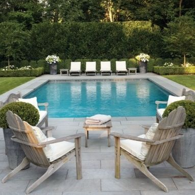 Grass, grey stone paving, gorgeous pool furniture and I love the potted  flowers.