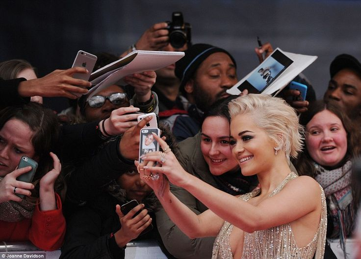 Rita Ora loves her fans welcoming her to the BRITs 2015 red carpet!