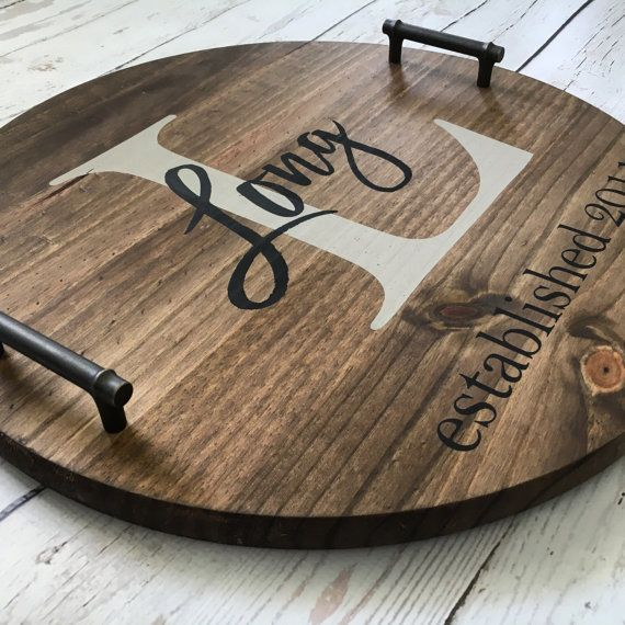 Our beautiful decorative serving tray makes the perfect statement piece for the home! This personalized, rustic tray would be a great addition to a coffee table, end table, or ottoman. What a unique housewarming, Christmas, or wedding gift idea! 18 round x 2 deep (with handles), this beautiful tray is stained a rich, medium walnut color and personalized with your chosen name/date options. Monogram initial is painted in a light gray and the name and date overlay are black. Colors may be…