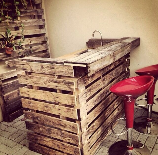 A bar made out of shipping pallets.. With running water!!  Rustic, I likey. - in the backyard
