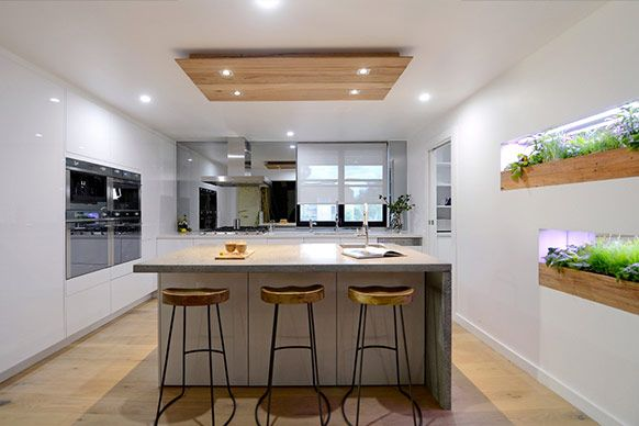 Best of 'The Block' Australia - Alisa + Lysandra's kitchen. This kitchen has it all - timber, concrete bench top, mirrored glass, reflective white cabinetry and greenery - but it all works. Light and bright.