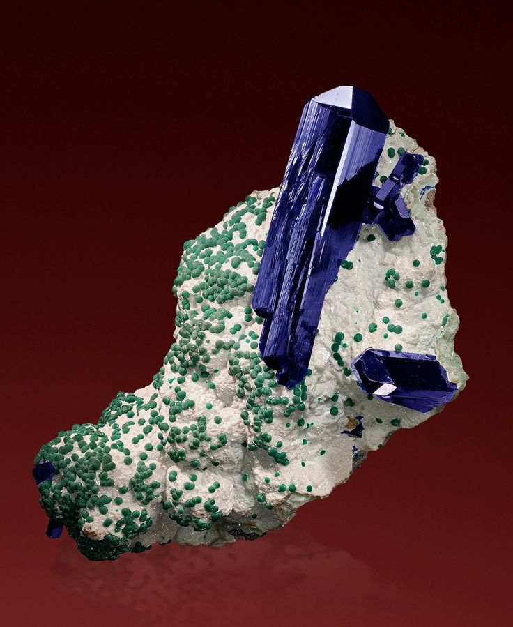 Azurite, Rosasite, Dolomite, Cuprian Smithsonite and Cerussite - Namibia        A doubly terminated, elongated azurite crystal resting on a matrix of cuprian smithsonite which is covered by white dolomite, and finally by plenty of small rosasite balls scattered around on the matrix.