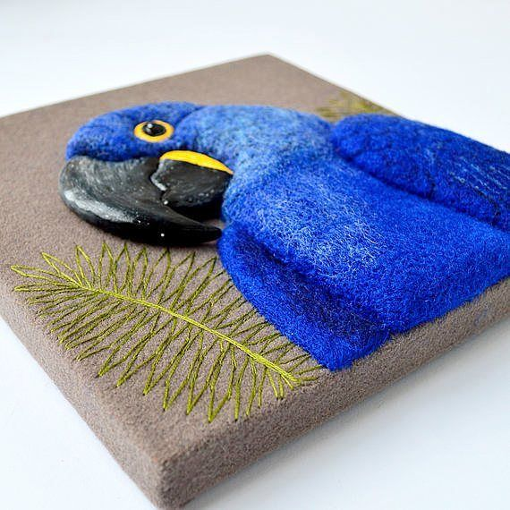 Needle felted 3D relief and palm tree leaves inspired embroidery on the Hyacinth Macaw wall art.
