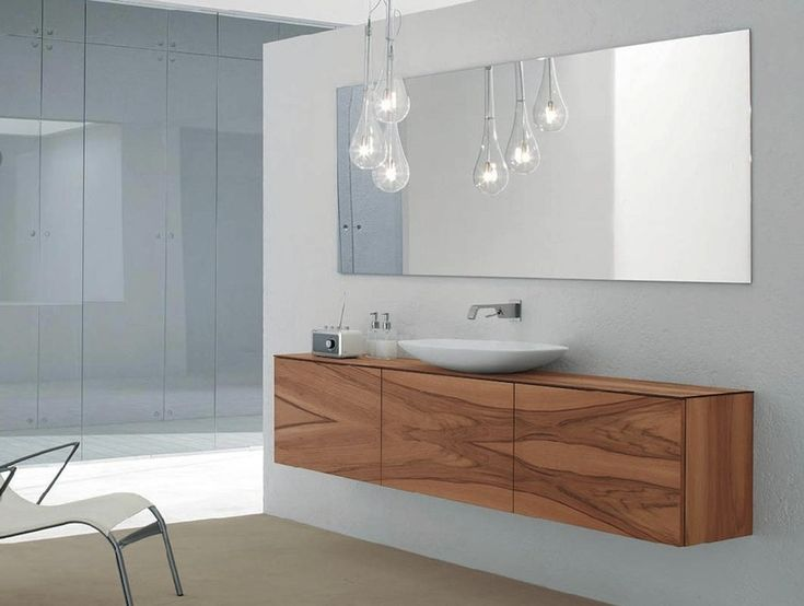 Wooden bathroom vanity and wood cabinet, also wall mounted mirror on white painted wall and also gorgeous pendant lamp. Pamper Your Home with These Amazing Wooden Bathroom Cabinets ➤To see more Luxury Bathroom ideas visit us at www.luxurybathrooms.eu #luxurybathrooms #homedecorideas #bathroomideas @BathroomsLuxury