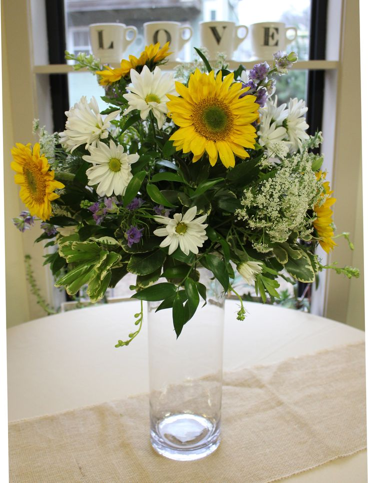 Summer style in a tall cylinder, decorated with birch ribbon overflowing with sunflowers and daisies, queen anne's lace, lavender larkspur, ruscus and pitt.  An excellent choice for a casual farm or outdoor wedding. - wedding flowers - 2018 weddings - Farm Weddings - Summer Weddings