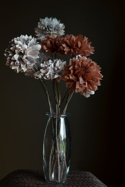 Here is the tutorial for tissue paper pom pom flowers:    For each flower you will need:    - 4 sheets of 5″ x 10″ inch tissue paper in color of your choice    – wire    - branch that is 12 to 20 inches long    -glue gun    Cut 5″ x 10″ rectangles of tissue. Stack four sheets and make 1/2 inch folds. Follow instructions for DIY pom poms to make the flowers.    Use a glue gun to adhere the flowers onto sticks.