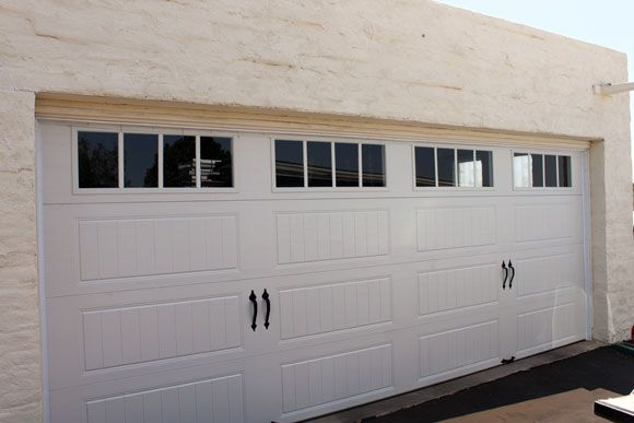Photo #9: THE RESULTS: The smooth operation of the new Clopay Gallery Collection garage door is a huge improvement over the old door. The grooved panel design, decorative hardware and windows  enhance the home's curb appeal. My parents feel they have the best looking garage door in the neighborhood. www.clopaydoor.com.
