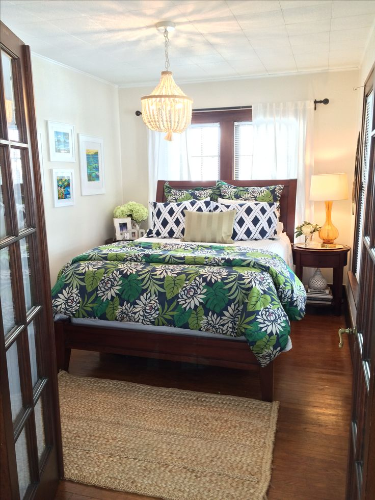 British colonial inspired Hawaiian bedroom. Dark mahogany woodwork, wood beaded chandelier, jute rug, Murano styled lamp, bedding from the tropics, and Heather Brown artwork all create a relaxing island getaway.