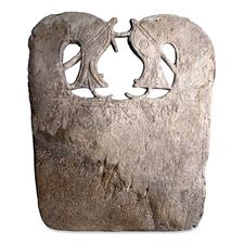 Whalebone plaque. 9th century CE, from a barrow burial at Lilleberge, Namdalen, Norway. For smoothing linen. This whalebone plaque is decorated with a pair of openwork horses' heads at the top and incised, ring-and-dot and geometric designs. It was found in a burial beside a woman's body, with a pair of oval brooches and strings of glass beads on the chest. In the British Museum.