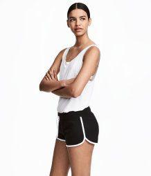 Svart. Ett par korta shorts i sweatshirtkvalitet med kontrastfärgade kantband. Resår och dragsko i midjan. En bakficka.