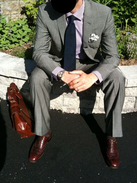 Dark brown leather accessories on a light grey suit