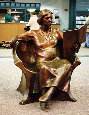"""""""Come Read With Me"""" - bronze statue by Tuck Langland; life-size statue in a library in Goshen, Indiana; 4' H x 4' W x 4' D; """"The librarian tells us, 'If there are children in the building, someone is in her lap.' The little ones talk to her and hug her goodbye. Even preteens sit there reading a book while waiting for a ride home."""""""