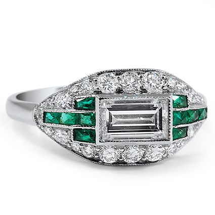 This breathtaking modern estate ring is brimming over with vintage style. An emerald cut diamond in an East-West bezel setting is the stunning centerpiece, and ten lab-created emerald baguettes and twenty-six dazzling round brilliant diamonds surround the center gem in a chic and distinctive platinum setting (approx. 1.37 total carat weight).
