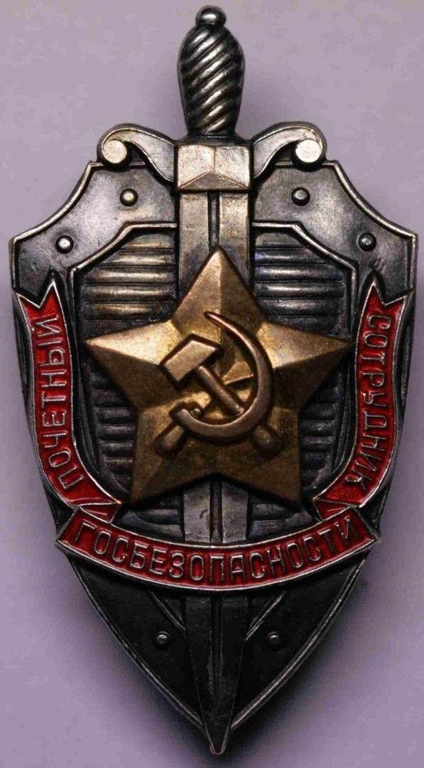 6 декабря 1957 года приказом КГБ при СМ СССР №115 был учрежден знак «Почетный сотрудник госбезопасности».  Форма и дизайн нового знака существенно отличались от прежних образцов. Это был слегка выпуклый фигурный щит, пересеченный вертикально мечом, в центре щита располагалась позолоченная пятиконечная звезда с серпом и молотом, обрамленная покрытой красной эмалью лентой с надписью «Почетный сотрудник госбезопасности».