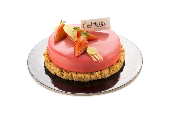Fashion: La mousse alla mandorla racchiude una marinatura di Fragole fresche, glassata con una glassa al cioccolato bianco colorata di rosa, viene poggiata su un disco di crumble alla mandorla amara.