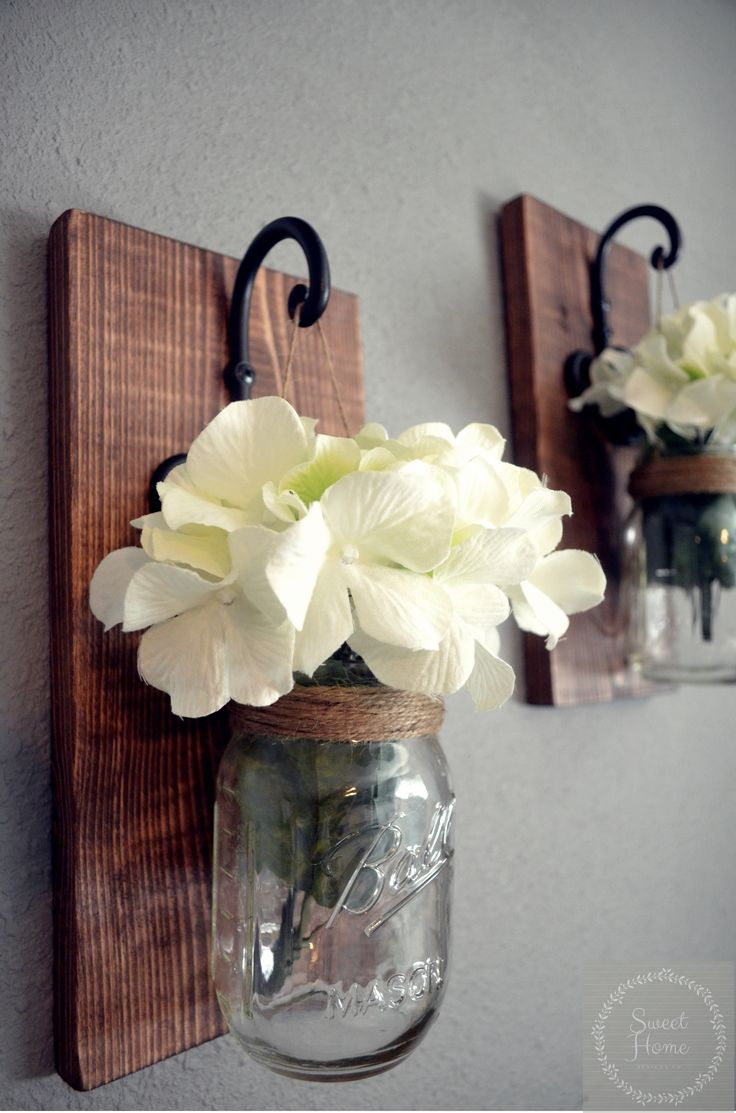 These rustic country style mason jar sconces are the perfect touch to your home decor. They bring warmth and beauty to any room. Comes in a set of 2!!! (Flowers are optional)  Our sconces are beautifully hand crafted using reclaimed wood. The wood is lightly sanded and stained in your choice of stain. Easy to mount and easy to maintain, they will only get better with time. The mason jars are hung with twine from gorgeous black cast iron hooks and they come ready to hang on your wall.