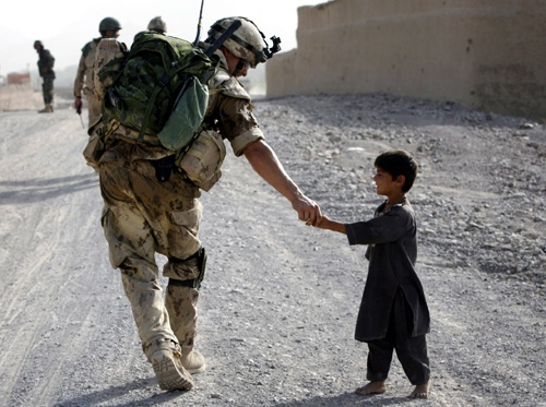 A Canadian soldier shakes hands with an Afghan boy during a joint patrol with Afghan National Army troops near Panjwaii village, Kandahar province,in July 2007