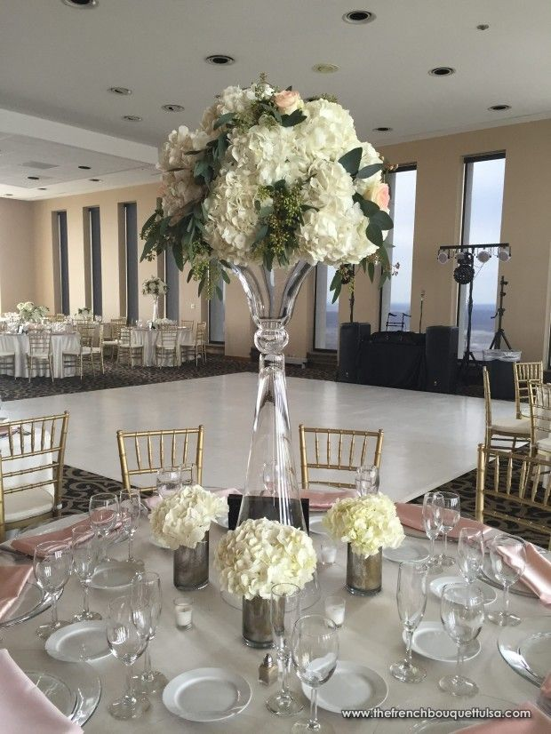 Tall white hydrangea and rose centerpiece in glass trumpet