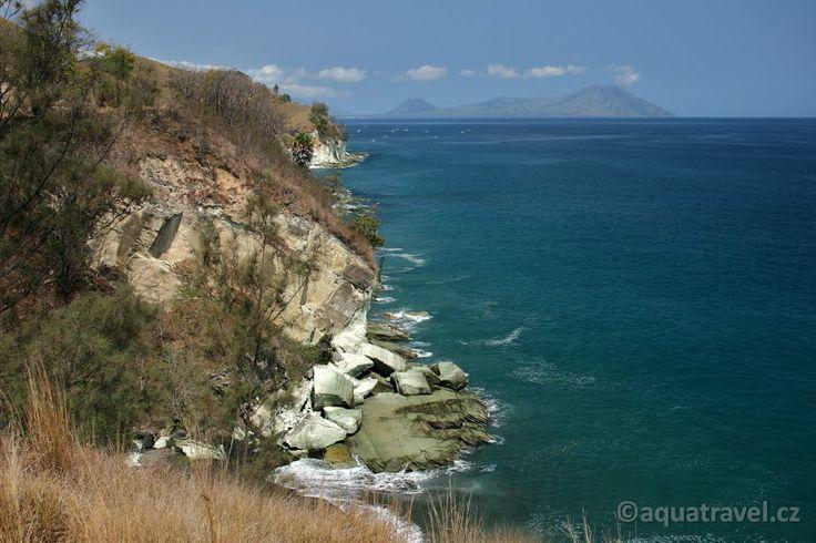 Ende, pobřeží se zelenými skalami i činnými sopkami na obzoru na konci světa.