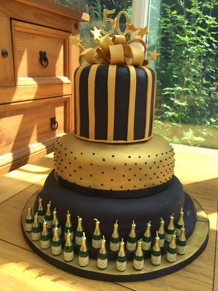 50th birthday cake celebration for black and gold theme party. Bottom layer vanilla madeira and middle layer chocolate madeira with chocolate ganache covered with chocolate fondant icing and sprayed with edible gold lustre. Top layer is a dummy.