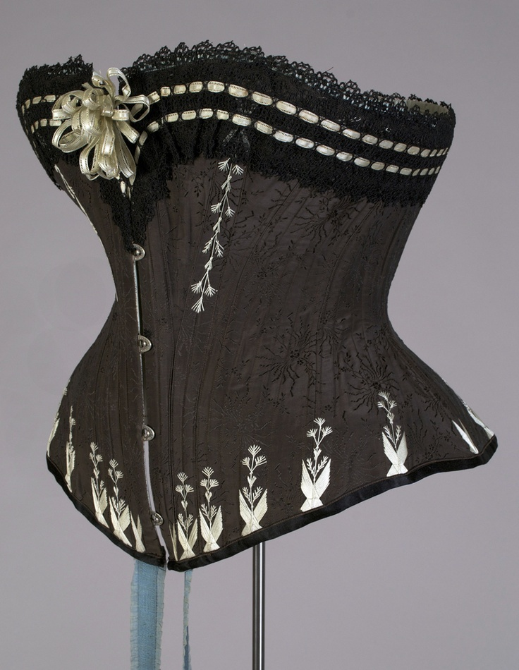 ~Corset. Polish, 1880s Black silk jacquard trimmed with pale blue green embroidery and black lace; blue elastic stocking supporters. Label: Marie Grochovska a Varsovie~ Fabourg de Cracovie No 39. Silverman/Rogers collection, KSUM 1983.1.1500
