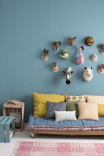 Loving these beautiful blue walls for a kids room with faux taxidermy decor and tons of pillows on a low daybed