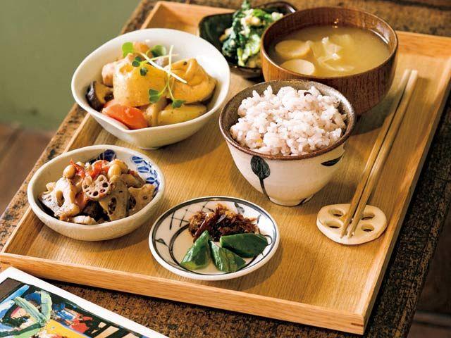 《 初台 》野菜中心の定食は¥1,000。この日は新じゃがと鶏肉の煮物、蓮根のカレーきんぴらなど。チキンカレー¥1,000もあり  おしゃべり禁止!夜定食のあるブックカフェ  『fuzkue』  カフェ  一見ブックカフェの佇まいだが、「ひとりの時間をゆっくり過ごしていただくための、静かなカフェというかバーというか食事処というか喫茶店というか…そういう店」と店主。コーヒーやビールもあれば丁寧に下ごしらえした野菜たっぷりの定食までそろう。   連れとの会話禁止、電話禁止とルールもあるが、店員に話しかけられる煩わしさはないし、店内の本は閲覧自由、長居歓迎という店はひとりにとって貴重である。心地いい静けさの中、読書と滋味深い味わいに浸る夜を。