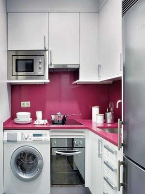 tiny pink & white kitchen: compact induction range + oven, compact microwave, full-sized refrigerator-freezer.  Even a front-loading washer for laundry.
