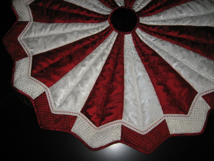 "48"" diameter red  white Xmas tree skirt. Designed in a complete round letting you rotate for even wear  lasting beauty. Machine quilted with red  white gimp. Metallic quilting on tips. $229  (Browse tree skirt collection at Hummingbird Gift Shop.)"