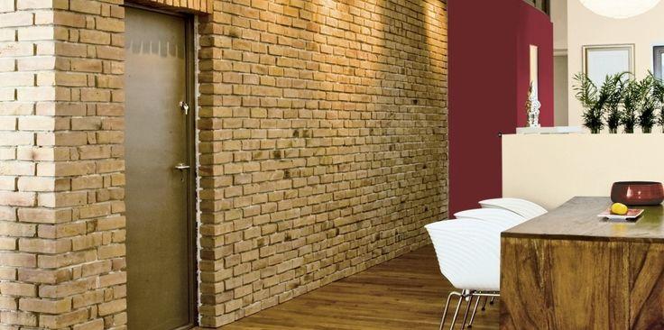 W tym wnętrzu doskonale połączono lekko industrialny styl z aranżacyjnym ciepłem. Receptą na tak udane zestawienie jest odpowiedni dobór materiałów (cegła i drewno, łagodzące surowość betonu na suficie) oraz kolorów (energetyczna czerwień i odcień aromatycznego cappuccino).