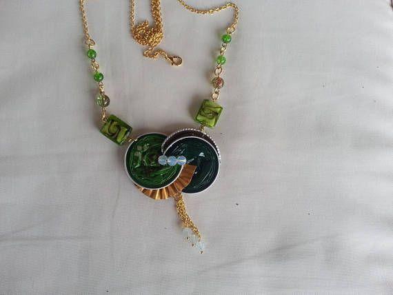 Très élégant collier composé de plusieurs capsules de café, vertes, dorées et marron, le pendentif est monté sur une chaine en métal doré sur laquelle jai ajouté des perles en verre vertes, au dessous du médaillon, un pendentif de trois chainettes terminées de perles translucides, comme