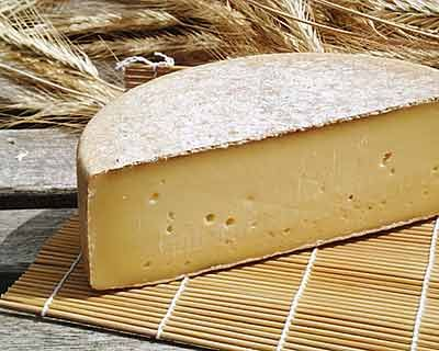 Gruyere  This is the classic 'mountain cheese' of France and Switzerland differentiated from the larger Ementhaller cheese by the much smaller or nonexistent holes