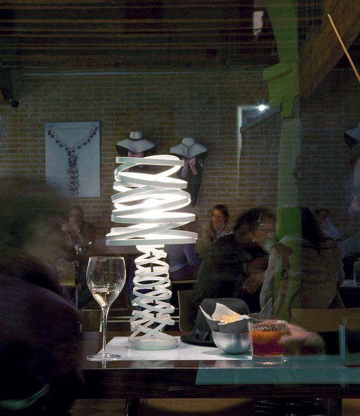 Lamparas de sobremesa de diseño italiano CURL MY LIGTH. Lampara realizada en metal con distintas secciones circulares en distintos planos. Luz difusa para crear un ambiente seductor y original. Disponible en dos colores, blanco y negro. 1 Luz de Rosca esférica de 150W. Altura de la pantalla 25cm. Modelo en negro lleva el cableado de luz en blanco y el modelo blanco lleva el cableado de luz en negro.