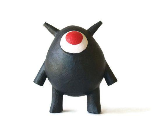 bicho raro negro con ojos rojos y cuernos  criatura de papel