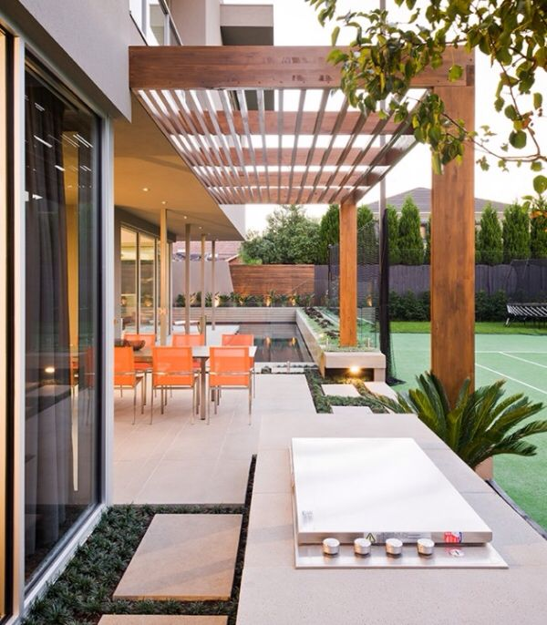 Pergola with built in fire place and tennis court view | adamchristopherdesign.co.uk