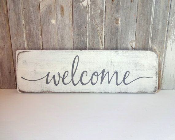 Hand painted wood sign, Welcome. Inspirational home decor.  *This sign is appx. 24 wide x 7.25 high. *The lettering is hand painted. *The base is a distressed white. *The lettering is a charcoal gray. *It includes a sturdy wire hanger already installed on the back. *If youd like to purchase more than one sign from my shop, I will package your signs together, (sizes permitting) and refund you whatever extra you paid on shipping. *Our signs are made for interior decorating. We do not…