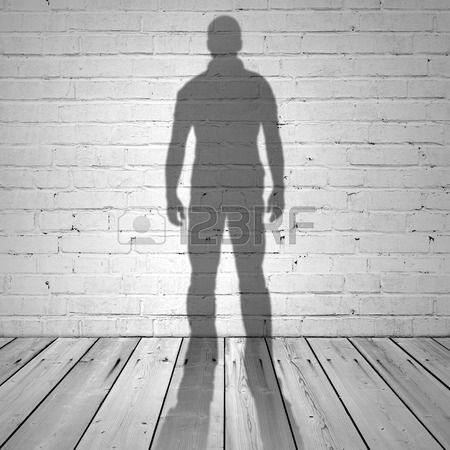 Sombra de un hombre en la pared de ladrillo blanco y el piso de madera Foto de archivo
