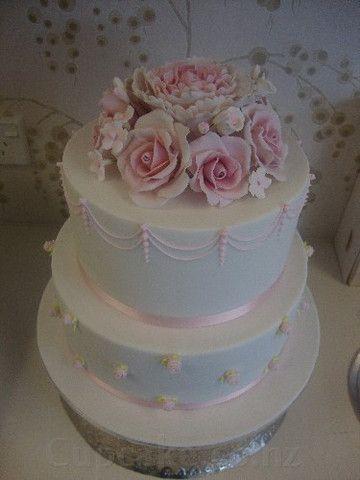 Elegant pink and white wedding cake with flourishes