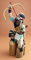 Hopi Kachina -- Left-Handed Hunter Kachina.             The Left-Handed Kachina, Siyangephoyadx, is one of the Hunter            Kachinas, and is always shown with a bow and arrow, and sometimes with            a throwing stick. He is called Left-Handed, because his gear is            reversed, and to draw an arrow from the quiver, he must use his right            hand, rather than his left as is normal.  (artist - Lowell Talshoma)