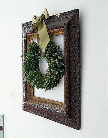 Framed Wreath:   For a fresh take on displaying your holiday wreath, highlight it in an empty vintage style picture frame. Fasten with a gold bow. Photo Credit: James Merrell