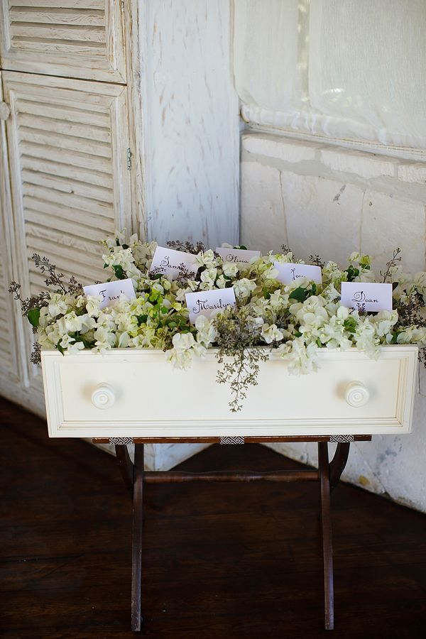 Vintage dresser drawer filled with flowers as escort card display.