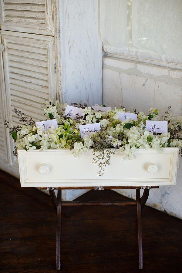 Vintage dresser drawer filled with flowers as escort card display.