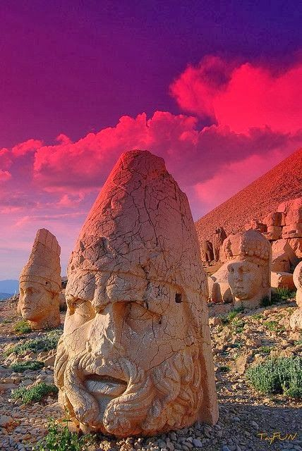 Nemrut or Nemrud is a 2,134 m (7,001 ft) high mountain in SE Turkey, a summit where number of large statues are erected around what is assumed to be a royal tomb from 1st century BC. In 62 BC, King Antiochus I Theos of Commagene built on mountain top a tomb-sanctuary flanked by huge statues (8–9 m or 26–30 ft high) of himself, 2 lions, two eagles & various gods statues were once seated, with names of each god inscribed on them. The heads of the statues have been removed & are now scattered