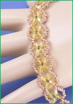 """Jewelry is made with small beads. Some are glass or stone. Adult supervision is recommended. This bracelet is made with Miyuki round 11/0 gold & green glass seed beads along with 4mm yellow ab Chinese bicone glass crystals and hooks with a trailer hitch or snap clasp. Measures approx. 7 1/8"""" long (including clasp) by 1/2"""" wide and is a design pattern from: Miss Ann. Priced at only $21.00 with """"FREE SHIPPING."""""""